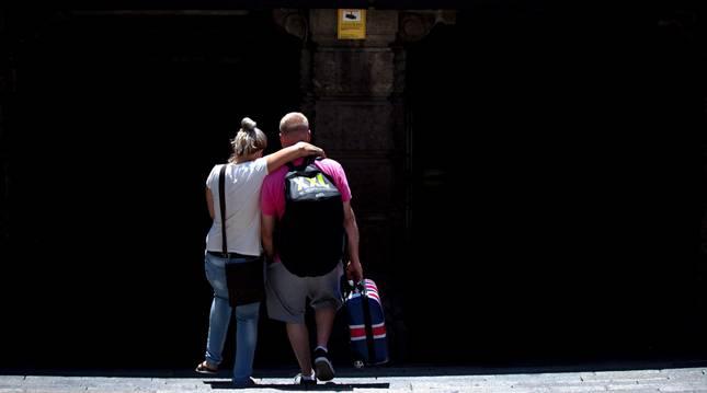 Una pareja de turistas británicos entran en en la estación de Renfe de Plaza Cataluña en Barcelona.