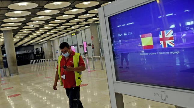 Un operario de Iberia pasa al lado de un monitor con las banderas de España y Reino Unido en la T1 del Aeropuerto de Madrid-Barajas.