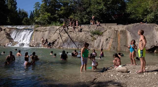Numerosas personas se han refrescado en los últimos días en los ríos navarros, como las de la imagen en Huarte.