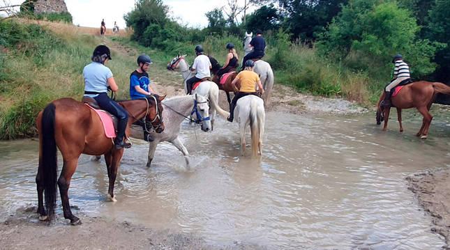 Varios jóvenes participan en un paseo a caballo dentro del programa 'Chancletas' del Ayuntamiento de Pamplona.
