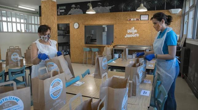 Foto de dos voluntarias preparando las bolsas de comida para los usuarios del servicio de atención a personas desfavorecidas Villa Javier.