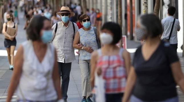 Foto de dos personas con mascarillas caminan por las calles de Madrid este sábado.