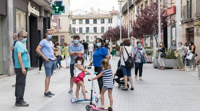 Un grupo de personas, con mascarilla, conversa en corro en una calle de Tudela.