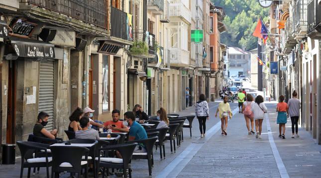 Varias personas toman algo en cafeterías y otras pasean en la calle Mayor de Sangüesa.