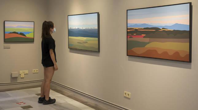 Una visitante contempla algunas de las obras de la exposición de Pedro Salaberri, titulada Caminos, que permancerá el mes de agosto en el Señorío de Bertiz.