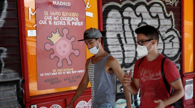 foto de Dos jóvenes pasean con mascarilla por una calle de Madrid