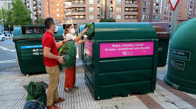 Una pareja mete la ropa en el contenedor situado en la calle Irunlarrea, en el barrio de Mendebaldea