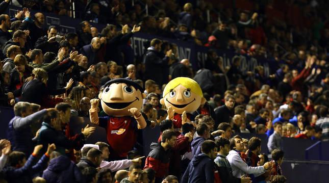 Las mascotas de Osasuna, Rojillo y Rojilla, en un partido de El Sadar, rodeadas de aficionados.