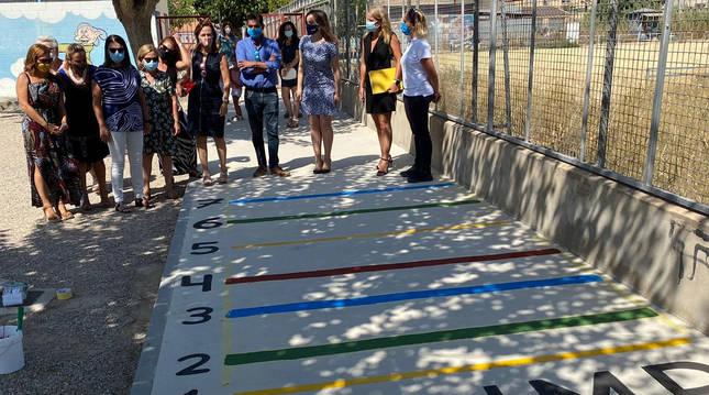 Varios padres atienden las explicaciones de un juego en un colegio de Murcia para que los niños mantengan la distancia de seguridad.