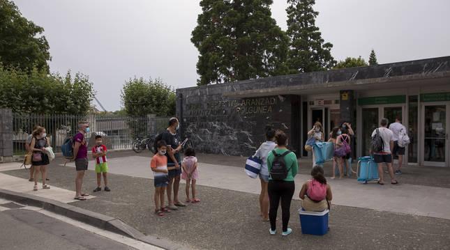 Foto de un grupo de personas, a la entrada de las piscinas de Aranzadi.