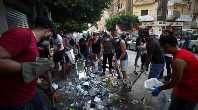 Varias personas limpian una calle de Líbano con escobas y palas.