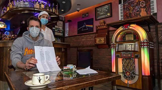 Jon Gorria junto a su madre María Jesús Plaza en el bar con la carta, las tazas y el imán.