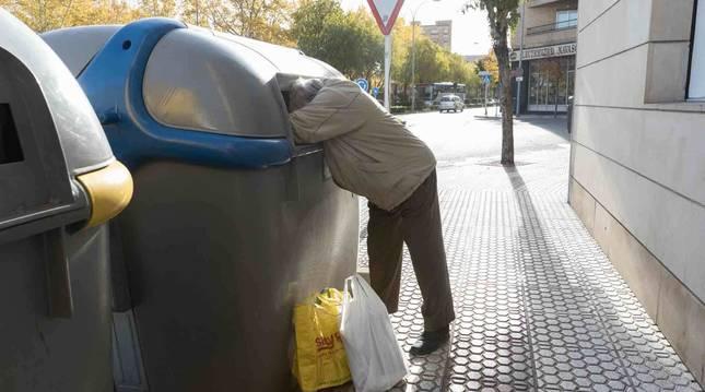 Un hombre rebusca en un contenedor de Tudela.