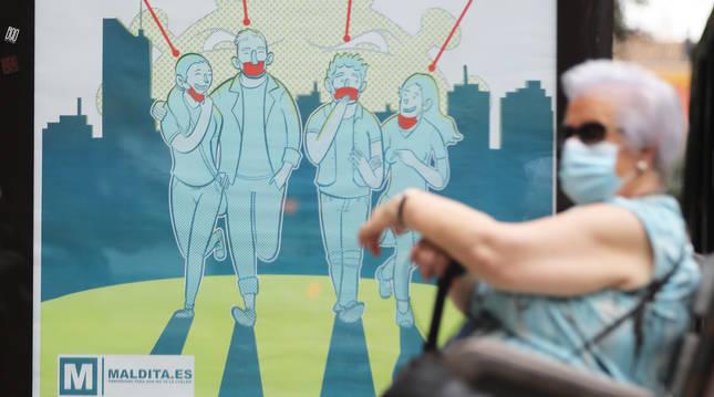 Una mujer espera en una parada con la mascarilla con un cartel de fondo.
