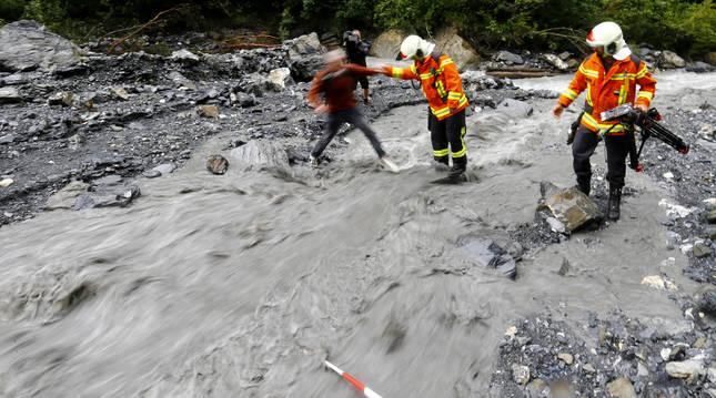 Bomberos suizos ayudan a cruzar a un periodista en la zona donde se busca al navarro desaparecido.