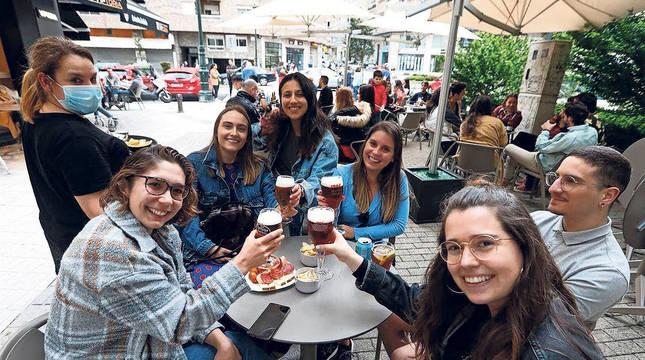 Un grupo de jóvenes celebra con cerveza y sin mascarilla en una terraza de un bar gallego.