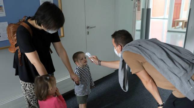 Un niño observa con atención el termómetro infrarrojo a su llegada a la escuela infantil.