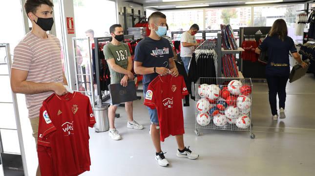 Aficionados de Osasuna en la tienda oficial adquiriendo las nuevas camisetas.