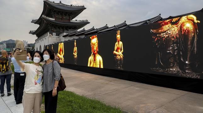 Dos mujeres con mascarilla se hacen un selfi en un museo callejero en Seúl.