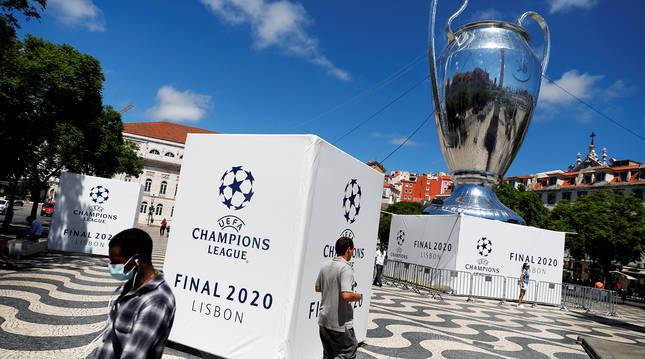 Varias personas caminan por una plaza de Lisboa ante una recreación gigantesca de la Copa de Europa.