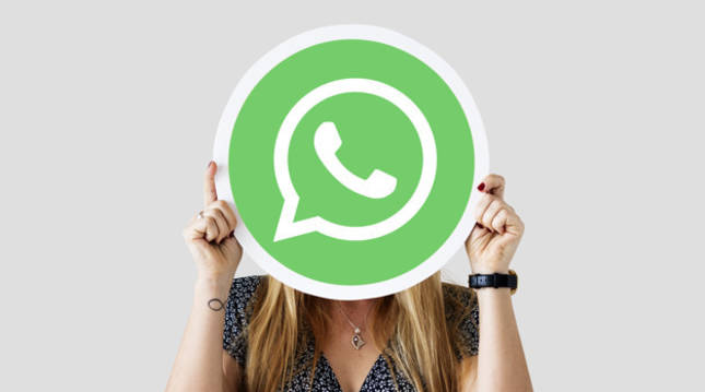 Una chica sostiene un logo de WhatsApp gigante