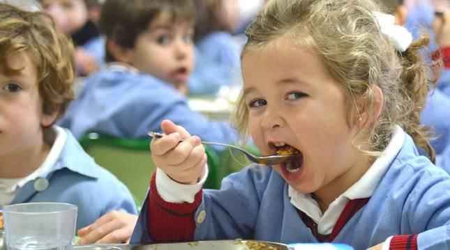 Foto de una niña comiendo un plato de arroz en un comedor escolar. En Navarra, cuatro de cada diez alumnos comen en el colegio.