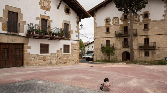 Un menor permanece sentado en una vía del entramado urbano de Iturmendi.