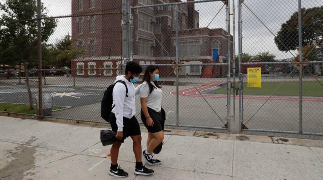 Dos personas caminan con mascarillas por el distrito de Queens de la ciudad de Nueva York.