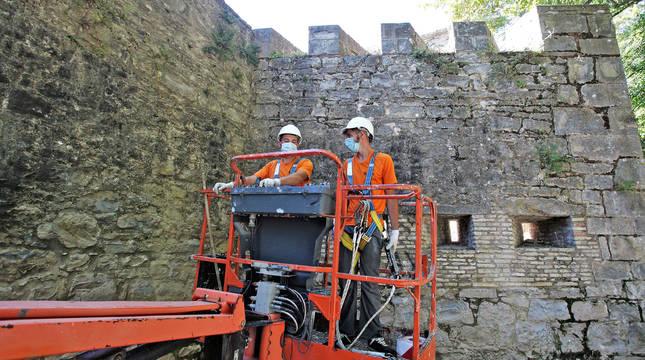 Dos operarios de Leache mueven el vehículo para retirar las malas hierbas de las cañoneras y merlones del fortín de San Bartolomé.