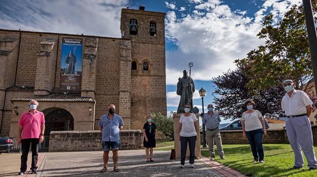 Algunos de los socios de la cofradía Amigos de San Veremundo en la entrada de la parroquia,  junto con la estatua del patrón de la localidad.