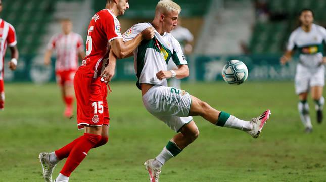 El delantero del Elche Daniel Escriche (d) intenta controlar el balón presionado por Juanpe, del Girona.