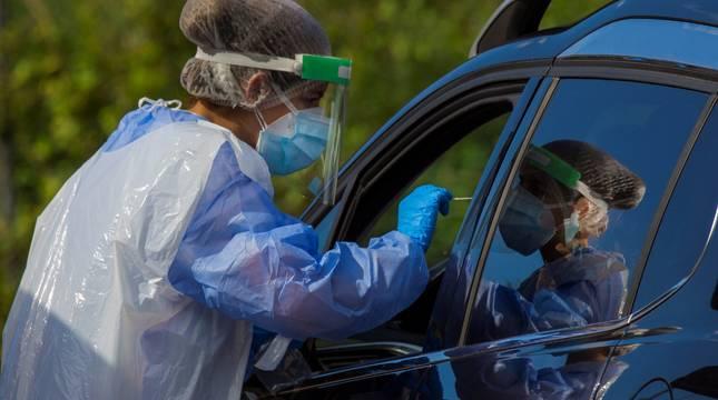 Personal sanitario practica la prueba PCR al conductor de un vehículo.