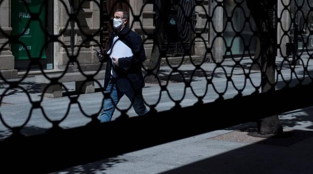 Un hombre camina por una calle por delante de la persiana semibajada de un comercio en los meses más duros de la pandemia.