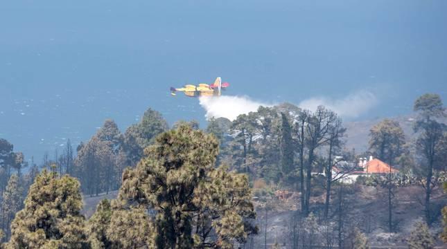 Un hidroavión hace una descarga este domingo para refrescar una zona quemada.