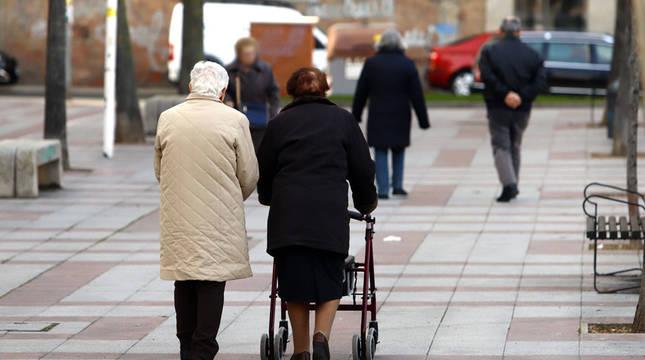 Una pareja de ancianos pasea por la calle.