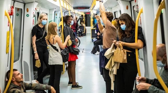 Foto de varios pasajeros con mascarilla, en el metro de Copenhague.