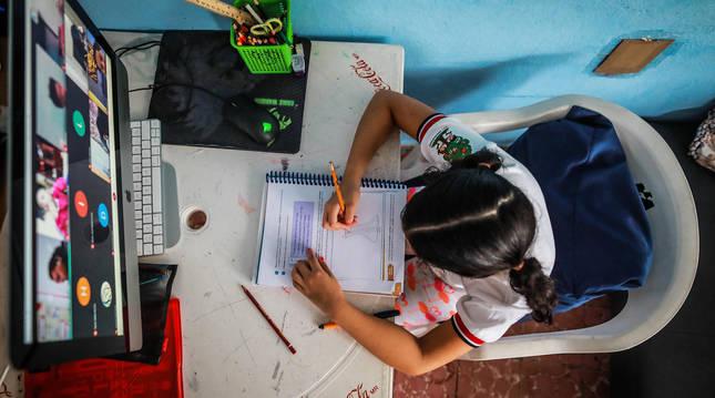 Una niña sigue desde su casa y a través del ordenador una clase virtual con sus profesores.