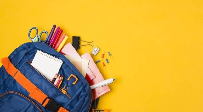 Imagen de una mochila junto a varios artículos de material escolar