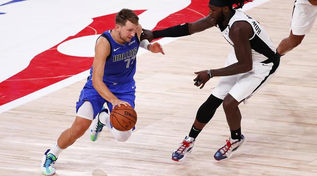Luka Doncic trata de marcarse del jugador de los Clippers, Montrezl Harrell.