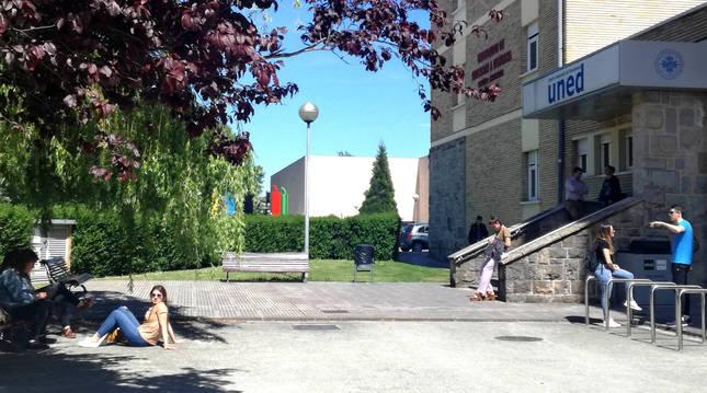 Estudiantes de UNED Pamplona conversan en la entrada al centro en una imagen previa a la pandemia. La Universidad apuesta por la docencia online.