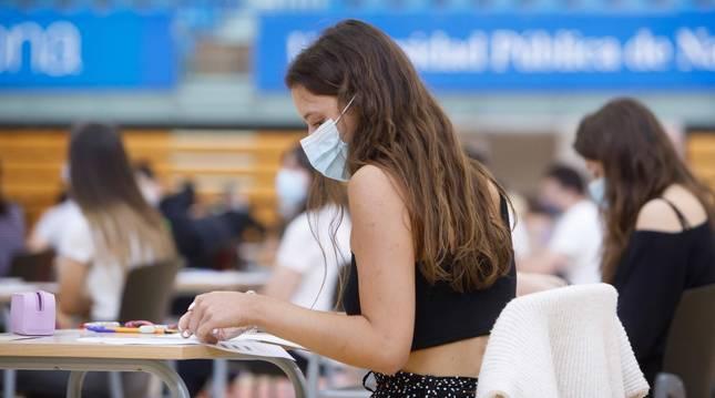 foto de Una joven se dispone a comenzar un examen de Selectividad en las pruebas de la EvAU en la UPNA. La mascarilla, obligatoria desde los 6 años.