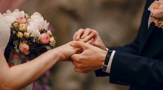 Un novio coloca el anillo a la novia durante su boda