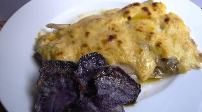 Foto de un plato de lubina al cava con chips de patata.