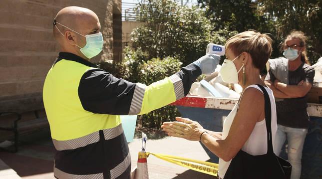 Un sanitario toma la temperatura de una voluntaria para hacerse una PCR en Puente de Vallecas, Madrid.