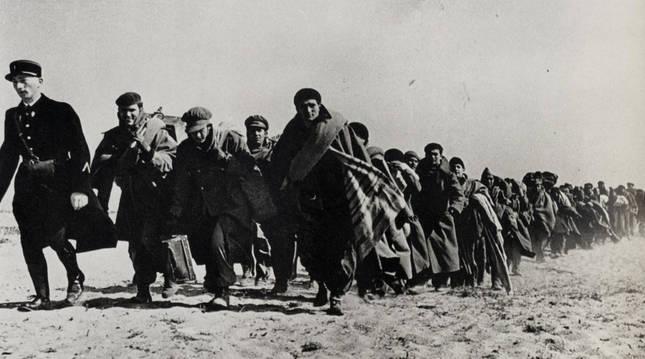 Un grupo de refugiados españoles marchan escoltados por un gendarme francés de un campo de concentración a otro en Le Bacarès (Francia, 1939). Esta imagen la captó el fotógrafo Robert Capa.