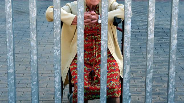 Foto de Montse, de 87 años, que recibía a su sobrina tras la puerta de entrada del centro en el que vive en Pamplona.