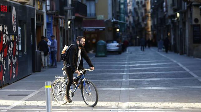 Foto de un ciclista por la calle Estafeta (Pamplona), sin apenas gente y con los comercios cerrados, tras decretarse el estado de alarma.