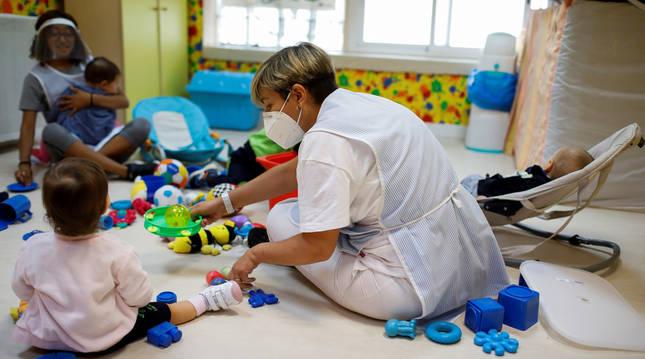 foto de Niños en una guardería con sus cuidadoras cumpliendo las medidas de seguridad