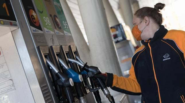 Foto de una empleada de la gasolinera San Rafael de Tudela se dispone a surtir de carburante a un vehículo.