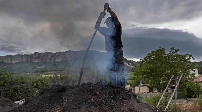 Apoyado en un palo, Miguel Lander Asarta remueve las entrañas de la carbonera (ubicada en Viloria) en la práctica conocida como 'Betagarri'.